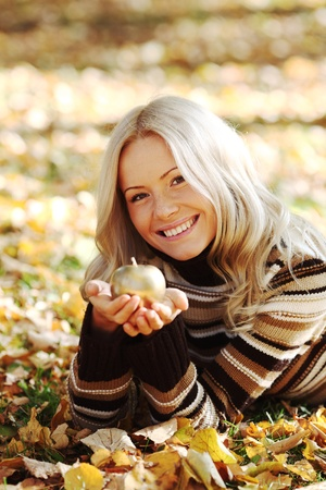 woman with golden apple in autumn park Stock Photo - 9862222