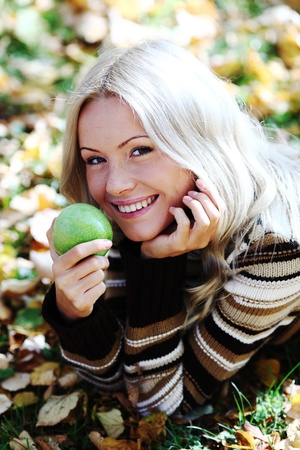 woman with green apple in autumn park photo