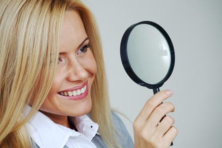 business woman looking through a magnifying glass photo