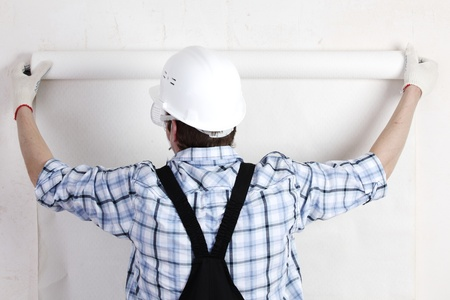 worker attaching wallpaper to wall Stock Photo - 9865055