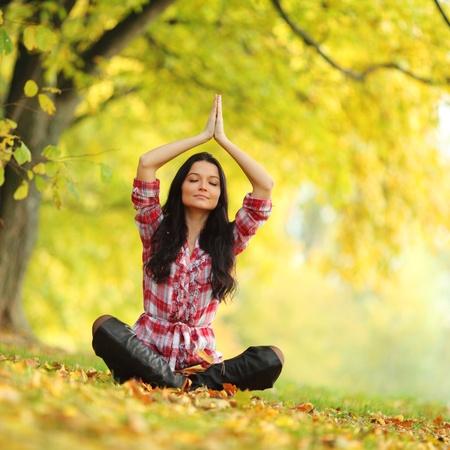 mujer meditando: mujer de yoga en bosque de oto�o en lotus plantean