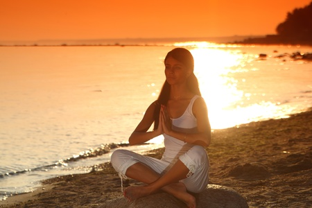 Young woman practicing yoga  near the ocean Stock Photo - 9907154