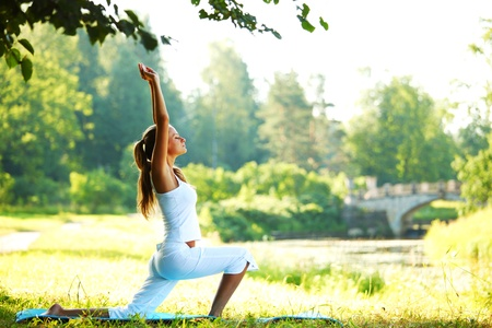 female pose: yoga woman on green park background Stock Photo