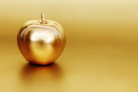 gold apple on gold background Stock Photo - 9903450