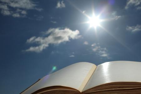 book of wisdom on sun sky background photo