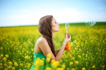 soap bubbles: Frau beginnt Seifenblasen auf gelbe Blume Feld