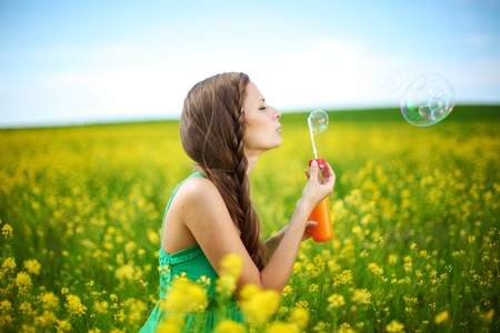 woman blowing: woman start soap bubbles on yellow flower field
