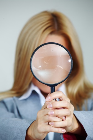 spy glass: business woman looking through a magnifying glass