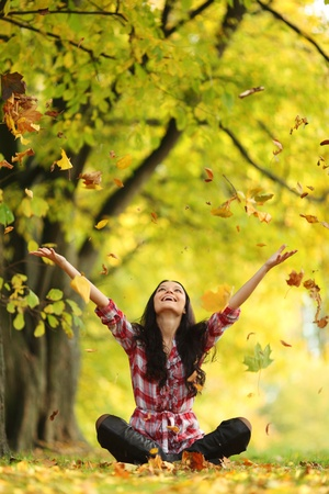 fall in love: woman drop up leaves in autumn park