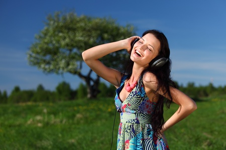 Young woman with headphones listening to music on field Stock Photo - 9961659
