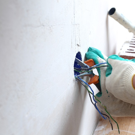electrical equipment: worker puts the wires in the wall Stock Photo