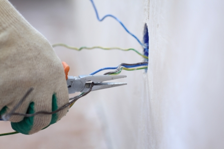 wiring: worker puts the wires in the wall Stock Photo
