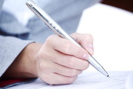 persona escribiendo: mujer escribir a l?z sobre papel Foto de archivo