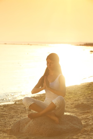 Young woman practicing yoga  near the ocean Stock Photo - 9961206