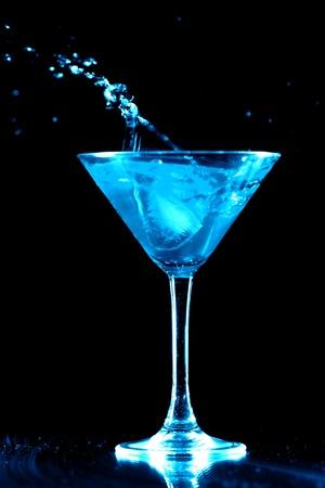 bartending: alcohol splash in martini glass on black background Stock Photo