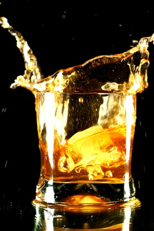 whiskey: whisky splash op zwarte achtergrond Stockfoto