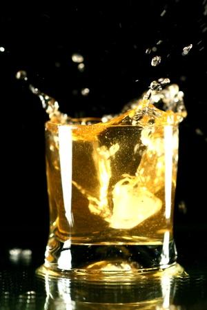 whiskey splash on black background photo