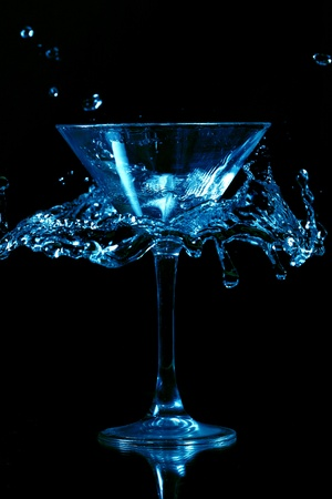 shaken: martini splash on black background close up