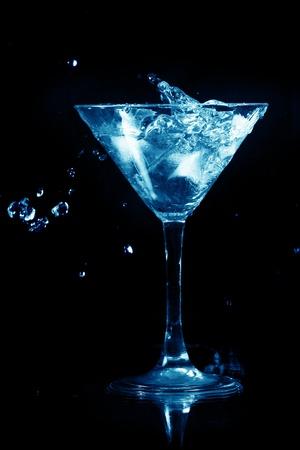 bartend: martini splash on black background close up