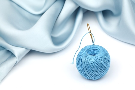 thread on blue silk isolated close up photo