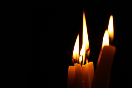 sacred candles in dark on black background