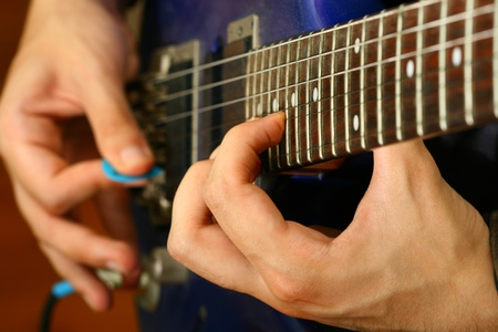 guitarists: man play solo on blue guitar