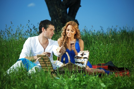 man and woman on picnic in green grass photo