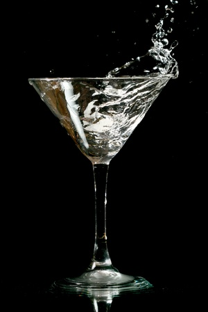 concoct: martini splash on black background close up
