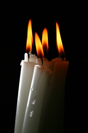 hope symbol of light: sacred candles in dark on black background