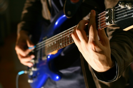 musical band: man play solo on blue guitar