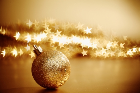 golden christmas ball on golden star bokeh background photo