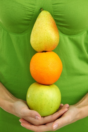 fruit pile in woman hands on white photo
