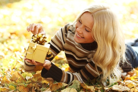 woman take autumn gift in park photo
