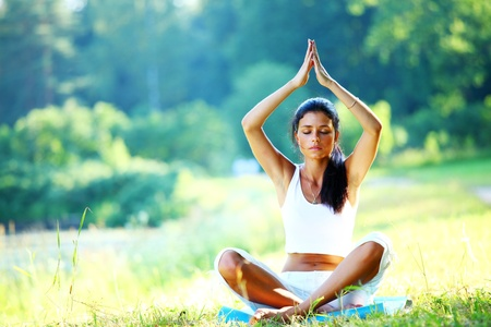meditating:  yoga woman on green grass in lotus pose