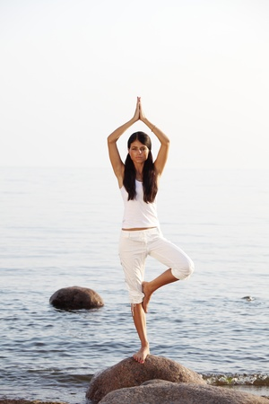 Young woman practicing yoga  near the ocean Stock Photo - 10260545