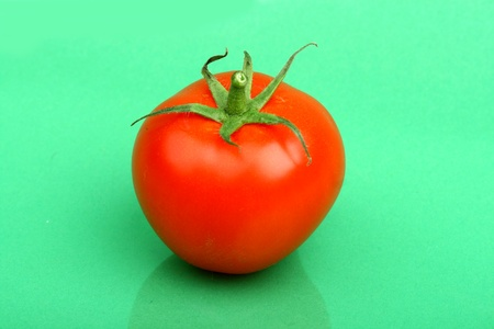 one tomato  on green background photo
