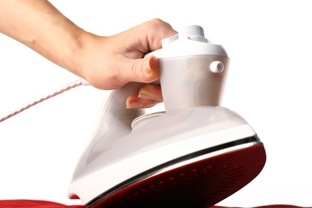Steam iron: girl hand have to iron red material