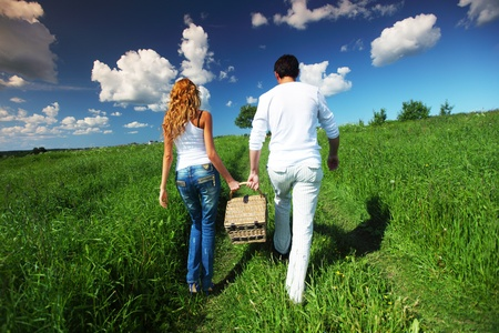 lifestyle outdoors: man and woman walk on picnic in green grass
