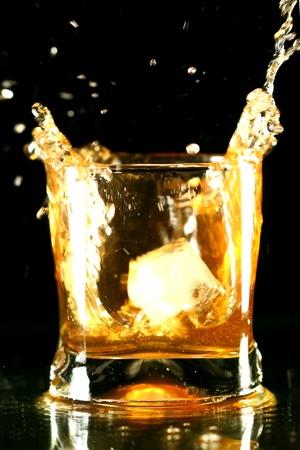 whiskey splash on black background Stock Photo - 10433333