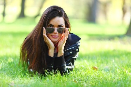 hands behind head: woman lay on green grass in park