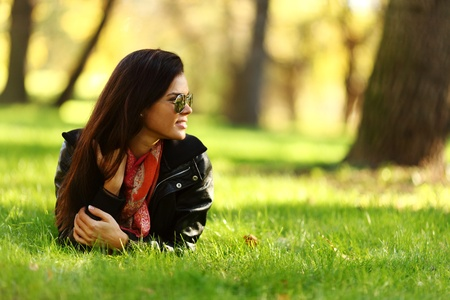 woman lay on green grass in park photo