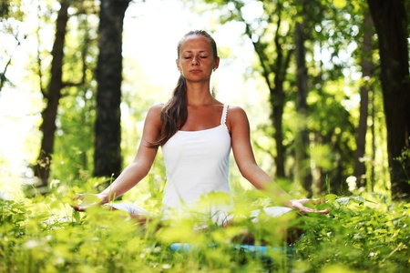 yoga woman on green grass in forest photo