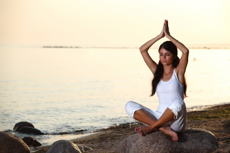 Young woman practicing yoga  near the ocean Stock Photo - 10435666