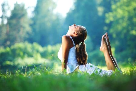 Kobieta jogi na tle zielonego parku