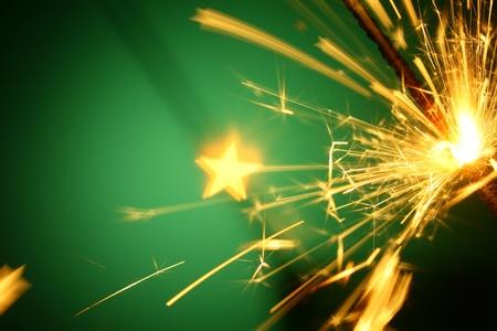 christmas sparkler on green background photo