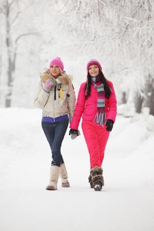 ropa invierno: dos mujeres de invierno ejecutan por nieve congelada alley Foto de archivo