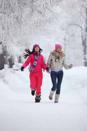 ropa de invierno: dos mujeres de invierno dirigido por callej�n de nieve congelada Foto de archivo