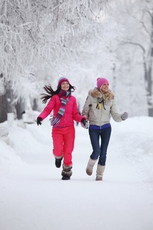 two winter women run by snow frosted alley photo