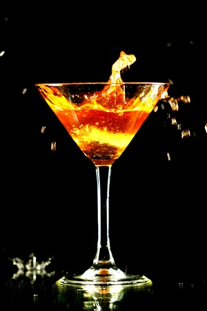 barman: alcohol splash in martini glass on black background Stock Photo