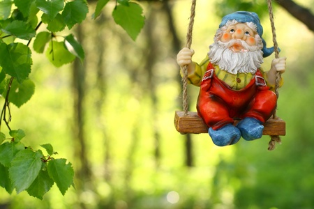 lawn gnome: garden dwarf on green background Stock Photo